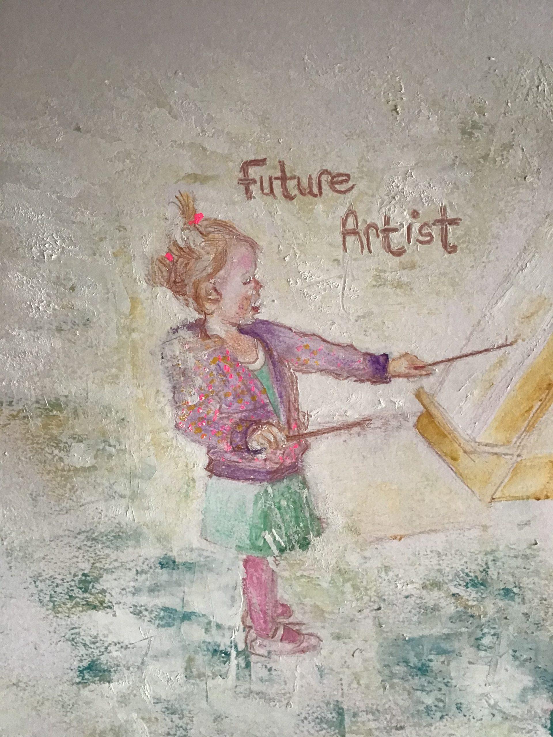 little girl painting at an artist easel